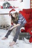 Smutna dziewczyna w szkockiej kraty koszula nakrętce Święty Mikołaj obsiadanie na krześle i Święty Mikołaj no przynosił prezentów Zdjęcia Royalty Free