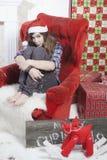 Smutna dziewczyna w szkockiej kraty koszula nakrętce Święty Mikołaj obsiadanie na krześle i Święty Mikołaj no przynosił prezentów Obrazy Stock