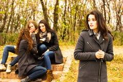 Smutna dziewczyna z przyjaciółmi plotkuje w tle Fotografia Royalty Free