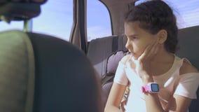 Smutna dziewczyna zanudzał obsiadanie w samochodzie w tylnym siedzeniu mała dziewczynka zanudzająca w samochodzie długa podróż zbiory wideo
