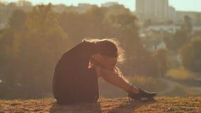 Smutna dziewczyny sylwetka siedzi samotnie w trawie i płaczu więc osamotniony zbiory