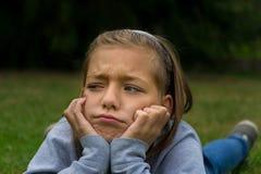 Smutna gypsy dziewczyna w ogródzie kłaść na żołądku osamotnionym Obraz Royalty Free