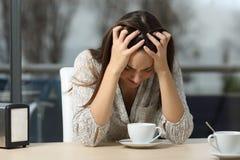 Smutna i przygnębiona kobieta samotnie w sklep z kawą Zdjęcie Stock