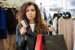 Smutna kędzierzawa młoda dama trzyma kartę debetową z torba na zakupy Zdjęcia Stock