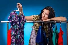 Smutna kobieta Pod Ubraniowym stojakiem Z sukniami Obraz Stock