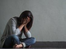 Smutna kobieta siedząca samotnie zamykał jej płacz i twarz podczas gdy zdjęcie stock