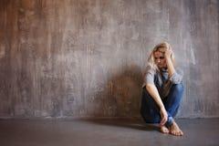 Smutna kobieta siedzi na podłoga Depresja i chroniczny zmęczenie Młoda piękna blondynka w szarym pulowerze i cajgach zdjęcie stock