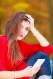 Smutna kobieta w parku z telefonem Zdjęcia Stock