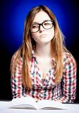 Smutna młoda dziewczyna z głupków szkłami i otwartą ćwiczenie książką Zdjęcie Stock