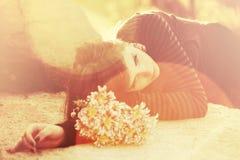 Smutna młoda kobieta kłama na nagrobku z kwiaty Zdjęcia Royalty Free