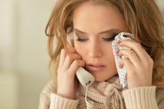 Smutna młoda kobieta opowiada na telefonie i płakać obrazy stock