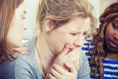 Smutna młoda kobieta pociesza przyjaciółmi Zdjęcia Stock