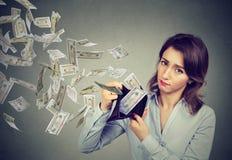 Smutna młoda kobieta pokazuje jej portfel z pieniędzy dolarowymi banknotami lata out daleko od fotografia royalty free