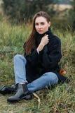 Smutna młoda kobieta siedzi samotnie na trawie outdoors nadzieja smucenie samotność jesień spadek przyjaciele leaf pod spaceru po Fotografia Stock