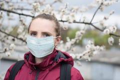 Smutna młoda kobieta w ochronnej medycznej twarzy masce Kwitn?cy drzewo na tle Wiosny alergia obraz royalty free