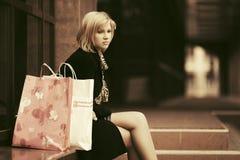 Smutna młoda kobieta siedzi na centrum handlowe krokach z torba na zakupy Obraz Stock