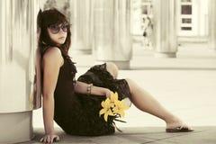 Smutna młoda kobieta siedzi na chodniczku z kwiaty Zdjęcie Stock