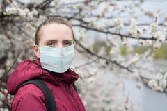 Smutna m?oda kobieta w ochronnej medycznej twarzy masce Kwitn?cy drzewo na tle Wiosny alergia fotografia stock