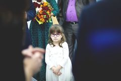 Smutna mała dziewczynka w biel sukni w tłumu przy ślubem zdjęcia royalty free
