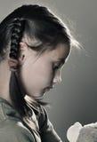 Smutna mała dziewczynka z zabawką na popielatym tle obrazy stock
