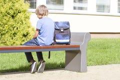 Smutna, osamotniona, nieszczęśliwa, rozczarowana chłopiec siedzi samotnie blisko szkoły, plecak Przypadkowi ubrania plenerowy Obrazy Stock