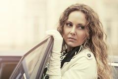 Smutna piękna mody kobieta w okopu żakiecie obok jej samochodu fotografia royalty free