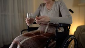 Smutna stara kobieta w wózku inwalidzkim bierze medycynę, wyzdrowienie okres, depresja obraz royalty free