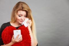 Smutna ze złamanym sercem kobieta patrzeje jej telefon Zdjęcia Royalty Free
