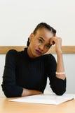 Smutna zmartwiona afrykanina lub czerni Amerykańska kobieta trzyma jej czoło z ręką przy biurkiem Zdjęcia Royalty Free
