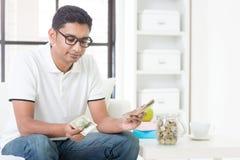Smutnego Indiańskiego faceta odliczający pieniądze obraz stock