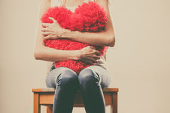 Smutnego nieszczęśliwego kobiety mienia czerwona kierowa poduszka Fotografia Royalty Free
