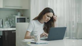 Smutnej kobiety pracujący laptop przy białą kuchnią Nieszczęśliwa osoba używa komputer zbiory