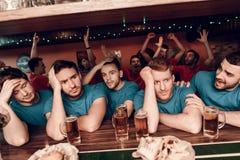 Smutni błękit drużyny fan przy barem w sporta barze z czerwieni drużyną wachlują doping w tle obraz stock