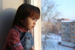 Smutni chłopiec spojrzenia z okno w wintertime Fotografia Royalty Free