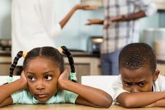 Smutni rodzeństwa przeciw rodziców dyskutować Zdjęcia Royalty Free