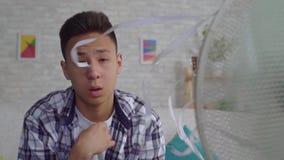 Smutniejący młody azjatykci mężczyzna ratujący od upału obsiadania przed pracującym fan wolny mo zbiory wideo