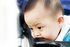 Smutny śliczny azjatykci dziecko ogląda out Zdjęcia Royalty Free