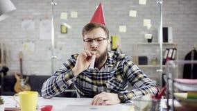 Smutny atrakcyjny ostrożny biznesmen świętuje osamotnionego urodziny w biurze, dmucha świeczkę na małym torcie zbiory wideo