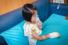 Smutny azjatykci dziecko trzyma maskowego opary inhalator dla traktowania astma zdjęcie stock