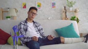 Smutny azjatykci młody człowiek z złamaną nogą w bandażach, kłama na leżance używa smartphone i patrzeć kamerę zbiory