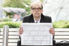 Smutny biznesmen z gazetą w jego ręki Obrazy Stock