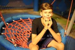 Smutny chłopiec chlanie na huśtawce Zdjęcie Royalty Free