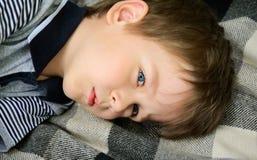 Smutny chłopiec lying on the beach na przyglądającym up i dywanie fotografia royalty free