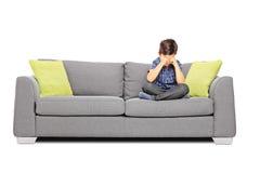 Smutny chłopiec obsiadanie na płaczu i kanapie obraz stock