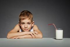 Smutny chłopiec obsiadanie z szkłem mleko Fotografia Royalty Free