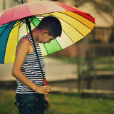 Smutny chłopiec withl tęczy parasol Zdjęcie Royalty Free
