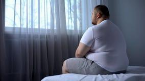 Smutny ciężki mężczyzny obsiadanie na łóżku w domu, problem zdrowotny, depresja, niepewność fotografia royalty free