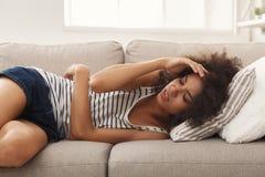 Smutny czarny dziewczyny uczucia bólu lying on the beach na kanapie obraz royalty free