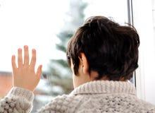 Smutny dzieciak na okno i zima śniegu Zdjęcia Royalty Free