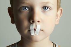 Smutny dzieciak z Uszczelnionym usta mały chłopiec Zdjęcia Stock